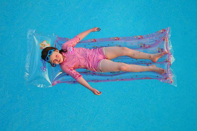dziecko na materacu niebieska woda